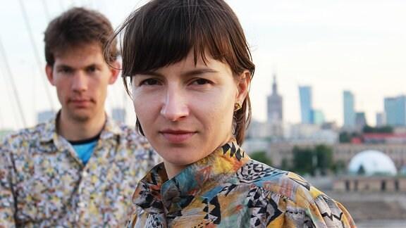 Junge Frau mit einem jungen Mann unscharf im Hintergrund.