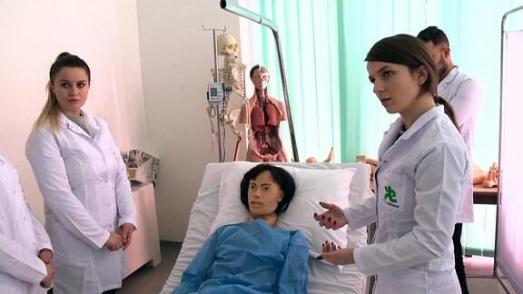 Junge Frauen im Kittel stehen um einen Patienten herum.
