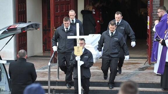 Männer tragen einen Sarg aus einer Kirche.