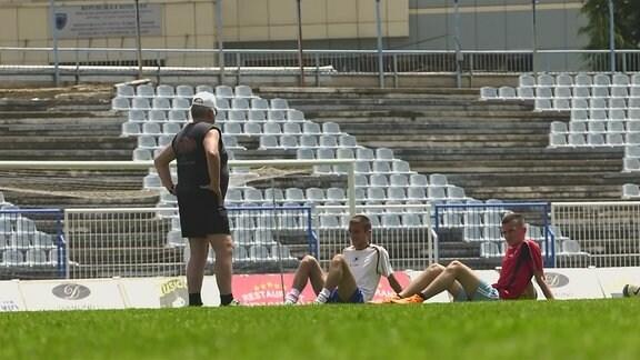 Männer sitzen auf einem Rasen