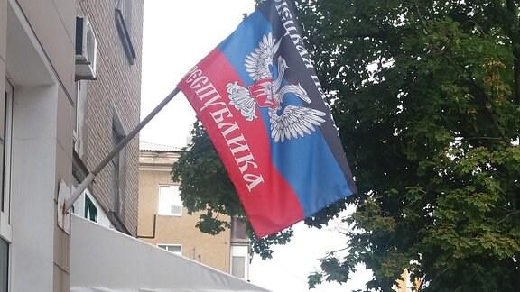 Flagge der Donezker Volkskrepublik hängt an einem Geschäft.