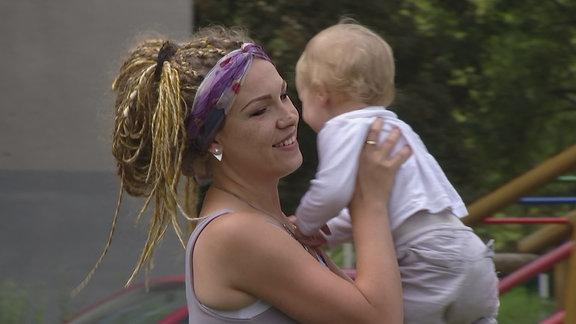Eine Mutter nimmt ihr Kind hoch