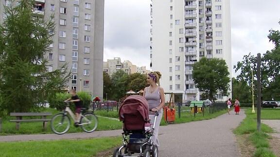 Eine Momentaufnahme eines Neubaugebietes. Eine Mutter schiebt einen Kinderwagen.