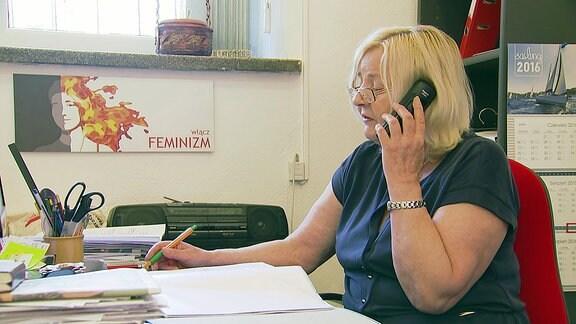 Eine blonde Frau telefoniert im Büro