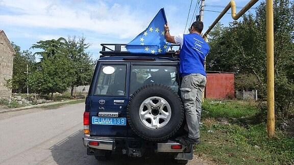Ein Mann befestigt eine EU-Flagge auf einem Auto