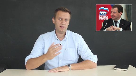 Ein Nachrichtensprecher, im Hintergrund das Bild von Dmitri Medwedew