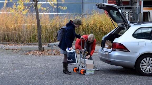 Zwei Frauen beladen den Kofferraum eines Autos.