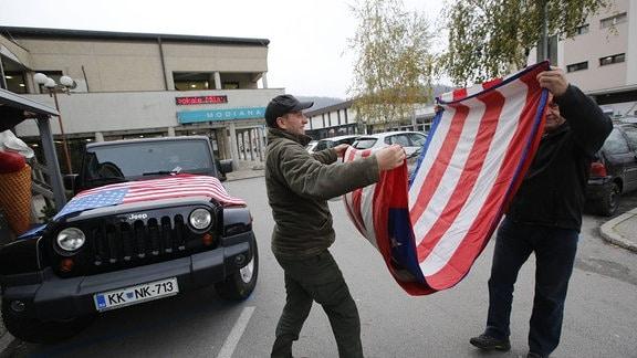 Zwei Männer falten eine Flagge zusammen.
