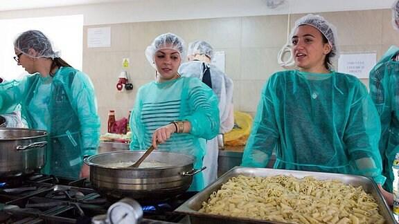 Junge Frauen in grünen Kitteln und Kopfschutz arbeiten in einer Küche