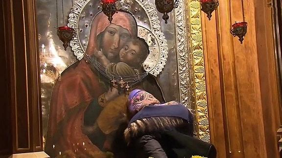 Eine Frau küsste eine Icone.