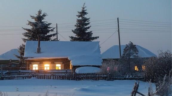 Häuser in Winterlandschaft bei Nacht.