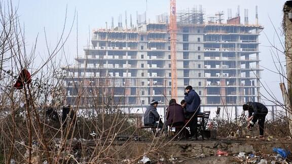 Im alten Belgrader Hafenviertel entsteht die Belgrade Waterfront – ein Stadtviertel mit Luxuswohnungen. Vor der Baustelle wärmen sich Flüchtlinge am Feuer.