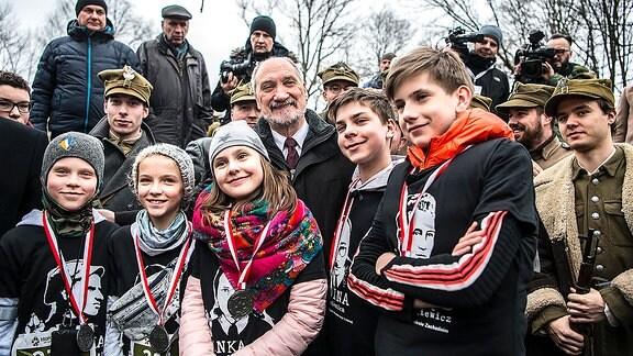 Kinder und Soldaten in historischen Uniformen posieren fröhlich vor der Kamera.