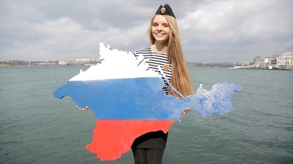 Kostümierte Frau hält weiß-blau-rot angemalte Form in ihren Händen