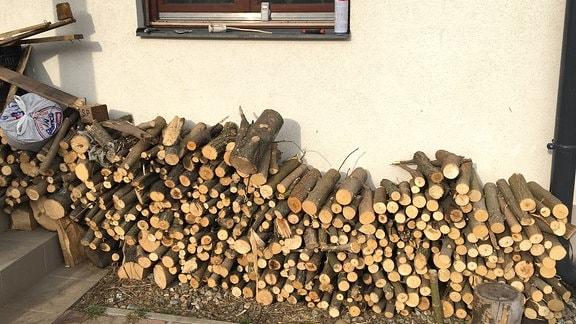 Gestapeltes Brennholz an einer Hauswand