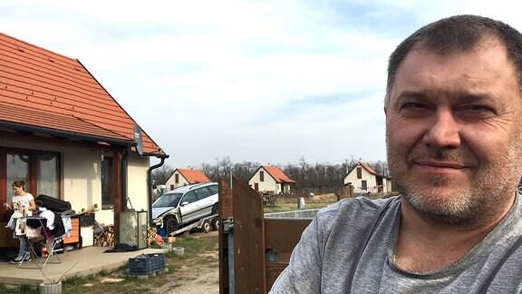 Ein Mann sieht in die Kamera, in Hintergrund ein Haus
