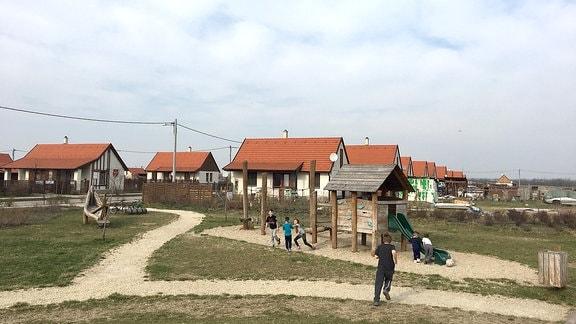 Kinder auf einem Spielplatz, dahinter Einfamilienhäuser