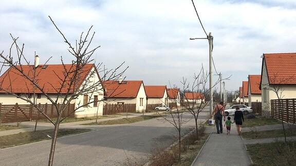 Menschen laufen auf dem Fußweg eine Straße entlang