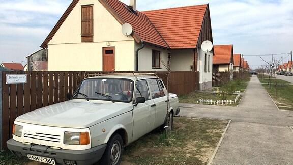 Ein Wartburg steht vor einem Einfamilienhaus