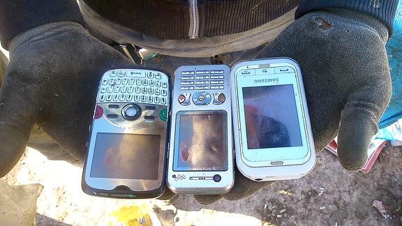 Zwei Hände halten drei Mobiltelefone