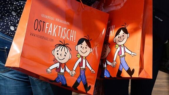 Orangefarbenen Papiertüten von der Eulenspiegel Verlagsgruppe mit den Zeichentrickfiguren Lolek und Bolek