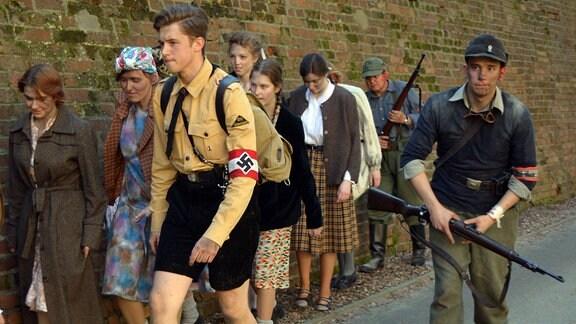 Verkleidete Jungen und Mädchen laufen an einer Wand entlang