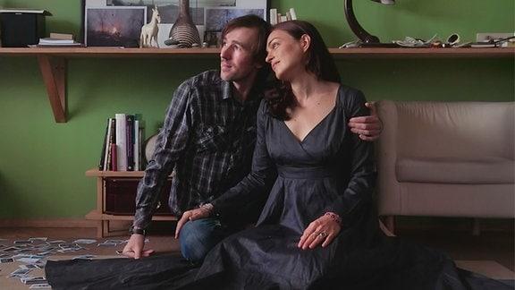 Zwei junge Leute sitzen auf dem Boden eines Zimmers