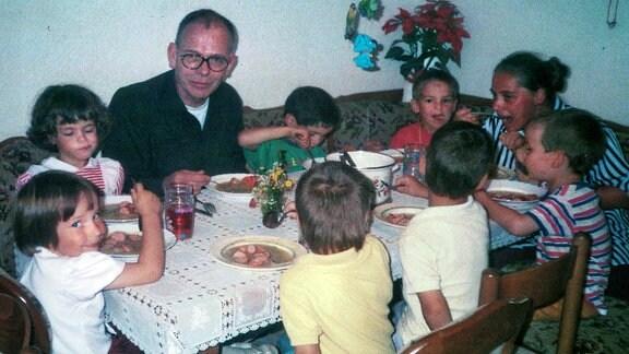 ein Mann und mehrere Kinder sitzen an einem Tisch
