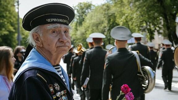 Ein Kriegsveteran im ukrainischen Kiew hält Mai-Nelken in der Hand