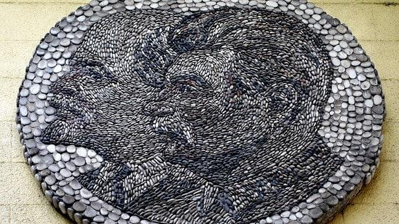 aus Flussteinen zusammengelegtes Mosaik, das Stalin und Lenin zeigt und an einer Seilbahnstation angebracht ist