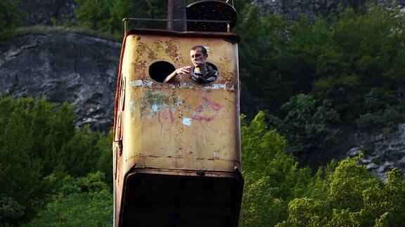 Ein Bergmann raucht eine Zigarette und lehnt sich durch das Kabinen-Bullauge der Seilbahnlinie Frieden, die vom Zentrum Tschiaturas zu einer Grube fährt.