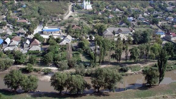 Blick in ein Tal. Zwischen Bäumen stehen Häuser und eine Kirche.