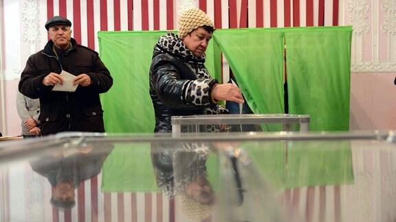 Eine Frau geht in Simferopol (Krim) wählen