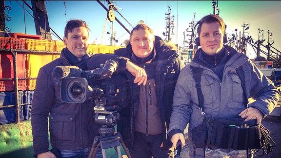 Drei Männer stehen neben einer Kamera