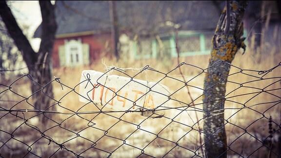 """Ein Schild mit der Aufschrift """"Post"""" auf russisch hängt an einem Metallzaun"""
