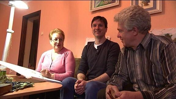 Zwei Männer und eine Frau sitzen auf einem Sofa