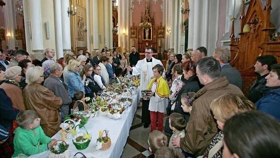 Ein Priester segnet Lebensmittel in einer Kirche am Karsamstag.