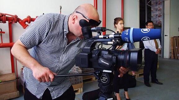 Mann bedient eine Kamera.