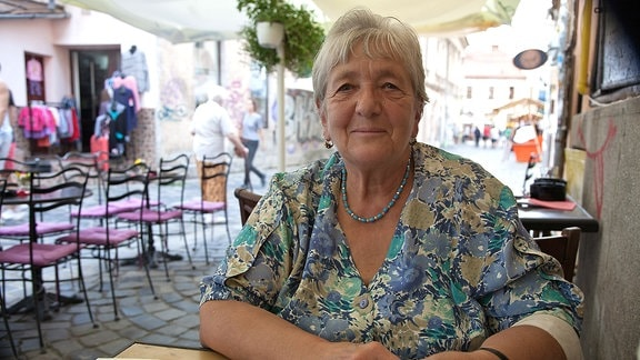 Eine ältere Frau sitzt an einem Tisch