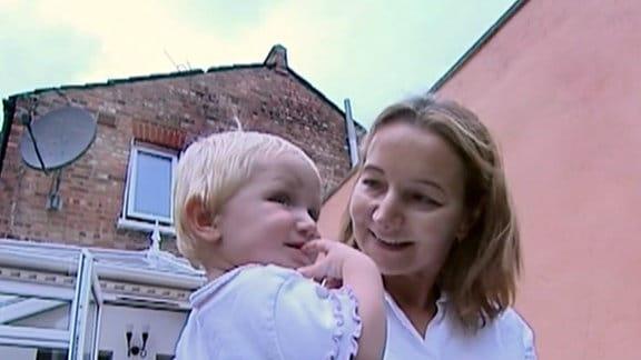 eine Frau hält ein Baby auf dem Arm