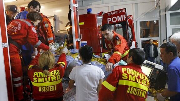 Eine verletzte Person wird aus einem Krankwagen transportiert, mehrere Sanitärer helfen dabei.