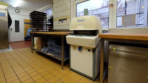 Blick in einen gefliesten Raum. Zwischen zwei Arbeitstischen steht eine kleine Maschine.