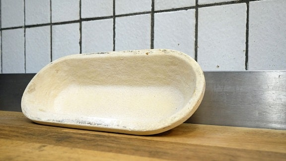 Ein kleines, ovales Gefäß aus Holz lehnt an einer Wand.