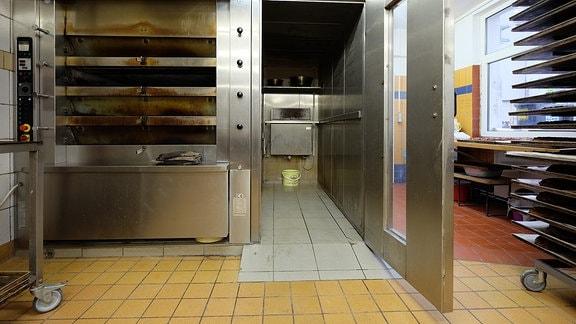 Ein großer Bäckerofen aus Edelstahl mit mehreren Schüben. Daneben ein offener leerer Raum.