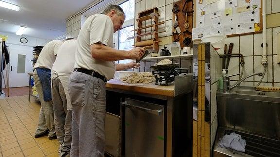 Drei Bäcker stehend nebeneinander am Arbeitstisch mit dem Rücken zum Betrachter