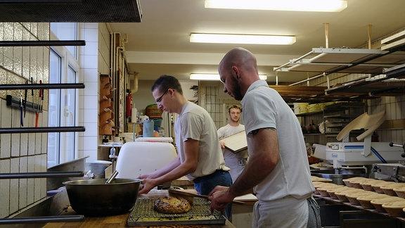Blick in eine Backstube. Drei Bäcker sind am arbeiten. Einer von ihnen bestreicht mit einem Pinsel eine Stolle.