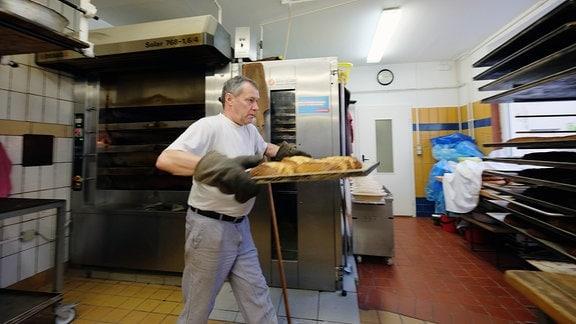 Mann trägt ein Blech vom Ofen weg.