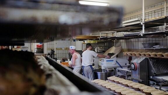 Blick in eine Backstube. Zwei Bäcker wirbeln herum. Es sieht nach Hektik aus.