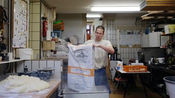 Ein junger Mann schüttet einen Sack Mehl in einen Metallbottich.