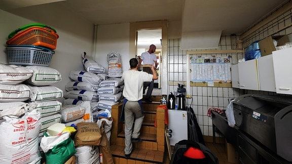 Zwei Männer tragen frisches Brot aus der Backstube in den Laden.